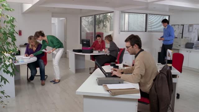 wide shot woman walking between desks with document in busy office/ paris - 忙しい点の映像素材/bロール