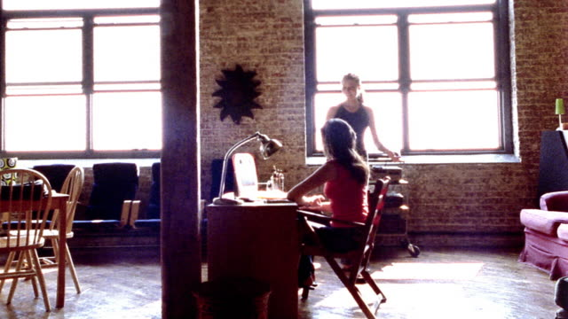 OVEREXPOSED wide shot woman walking up to woman sitting at desk in loft / both look at computer