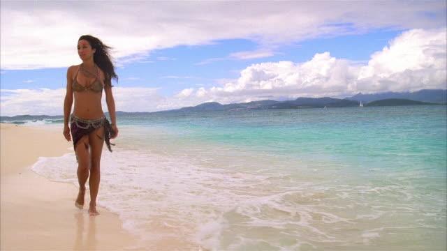 Wide shot woman wearing bikini walking along the beach at water's edge