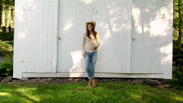 Wide shot woman wearing straw cowboy hat standing in front of white barn / laughing and walking away