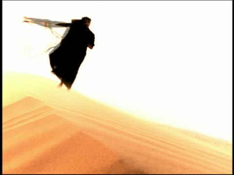 vídeos de stock e filmes b-roll de wide shot woman with black veil walking on desert dune with robe blowing in wind / egypt - super exposto