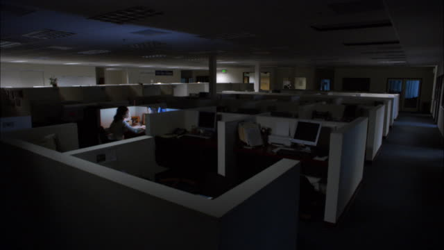 wide shot woman working late in cubicle in dark office / turning off light and leaving / empty office / low angle - computer monitor back stock videos & royalty-free footage