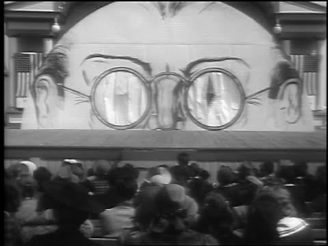 vidéos et rushes de b/w 1941 wide shot women in bikinis enter outdoor stage through pair of giant glasses / palisades park nj - concurrent