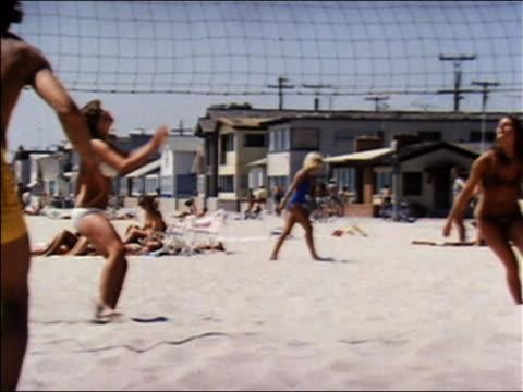 vídeos de stock e filmes b-roll de 1970 wide shot women in bikinis playing beach volleyball game / audio - biquíni
