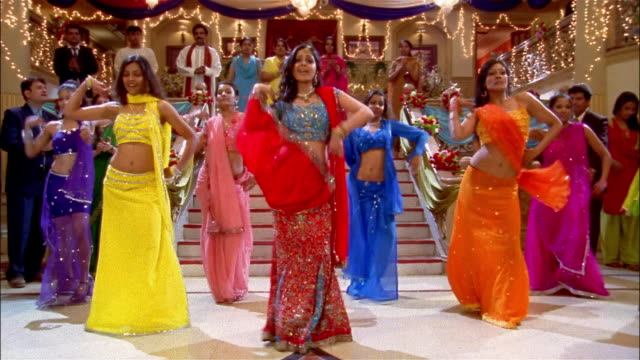 wide shot women performing bollywood-style dance number - bollywood stock videos and b-roll footage