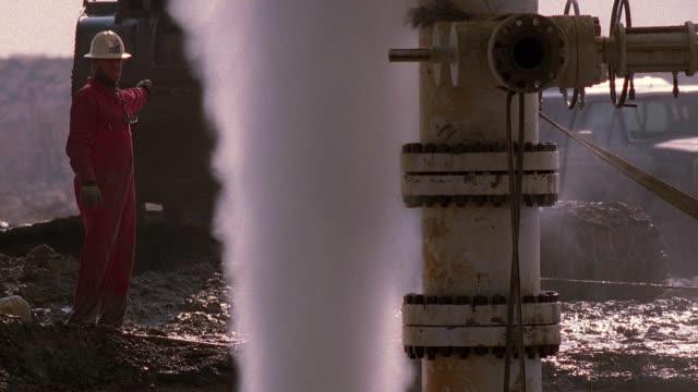 wide shot worker directing vehicle behind gas pipeline geyser / bakresfield, california - pipeline stock videos and b-roll footage