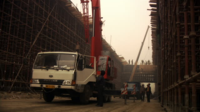 wide shot workers and cherry picker at construction site/ beijing,  china - cherry picker stock videos & royalty-free footage