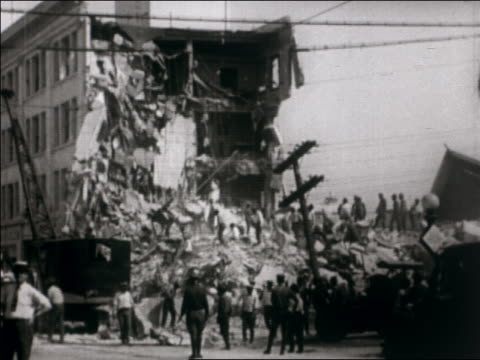wide shot workers clearing destroyed building after earthquake / santa barbara, ca / newsreel - anno 1925 video stock e b–roll