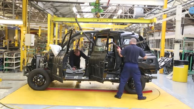 wide shot workers inside the factory of the london taxi company attach the body of a tx4 london taxi to its chassis on september 11 2013 in coventry... - fahrgestell stock-videos und b-roll-filmmaterial