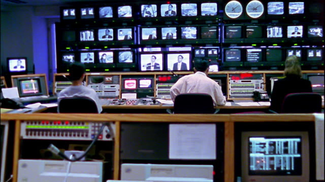 vídeos y material grabado en eventos de stock de wide shot workers sitting in television broadcast control room for cnbc asia bureau / hong kong - estudio de televisión