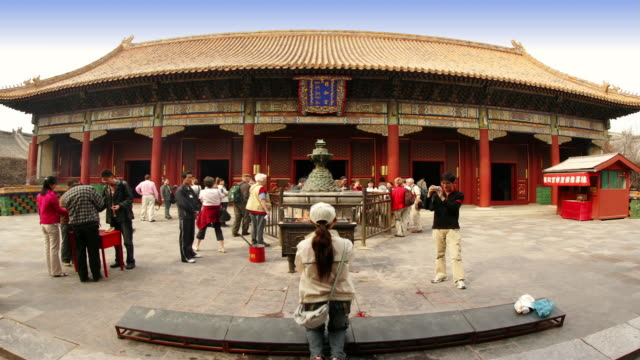 vídeos de stock, filmes e b-roll de wide shot worshippers lighting sticks of incense outside yonghegong dian hall at lama temple / beijing - 17th century style