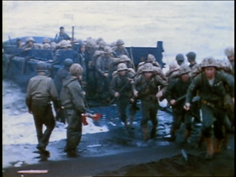 vidéos et rushes de wide shot ww ii u.s. soldiers disembarking from an amphibious craft onto the beach / pacific - world war ii