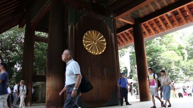 wide shot yasukuni shrine stands in tokyo japan on saturday aug 15 wide shot people walk past the japanese national flag displayed above the entrance... - chrysanthemum stock videos & royalty-free footage