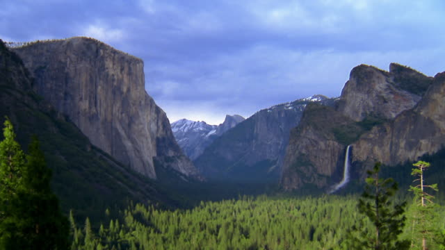 Wide shot Yosemite Valley with mountains and waterfall in background / Yosemite National Park, California