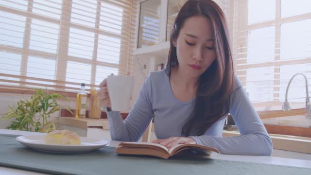 広いショットpov 若い大人のアジアの女性は台所で本を読んでいます。自宅でリラックスしながらアナログブックの歴史を勉強している女性。日々の生活活動で学び、知識、教育、リラックス - 本点の映像素材/bロール