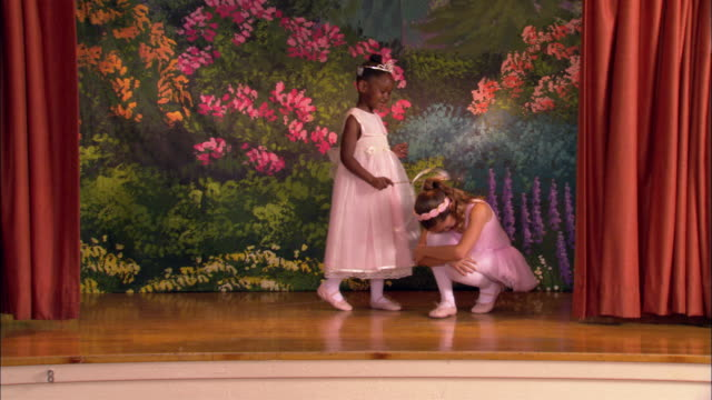wide shot young ballerina crouched down on stage / another girl tapping her with wand / ballerina dancing around younger girl - ballet dancer stock videos & royalty-free footage
