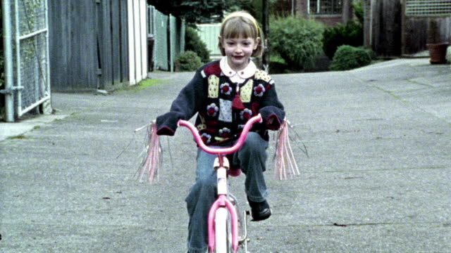 wide shot young blonde girl riding bicycle with training wheels toward camera / zoom in to close up face - stabilisers stock videos & royalty-free footage