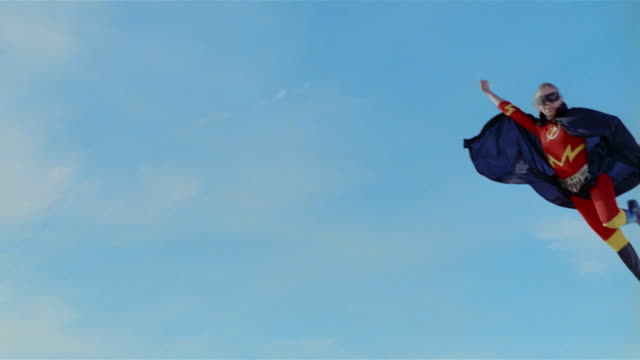 Wide shot young blonde woman in mask, cape, and superhero costume in midair simulating flying after jumping on trampoline