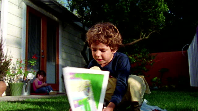 stockvideo's en b-roll-footage met wide shot young boy looking at book in yard with small girl sitting in background / california - prentenboek
