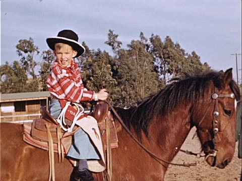 1940 wide shot young boy riding horse and wearing cowboy costume while man leads horse around corral / los angeles, california, usa  - image stock videos & royalty-free footage