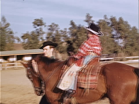 1940 wide shot young boy riding horse and wearing cowboy costume while man leads horse around corral / los angeles, california, usa  - 1940 stock videos & royalty-free footage