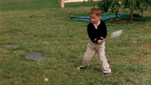 1958 wide shot young boy trying to hit golf ball with toy golf club on lawn - golf stock-videos und b-roll-filmmaterial
