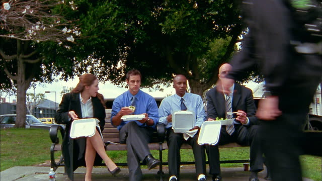 wide shot young business people eating lunch on park bench / cyclist and skateboarders passing them - bench stock videos & royalty-free footage