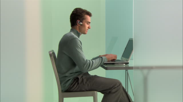 Wide shot Young businessman using laptop and talking on phone in modern office