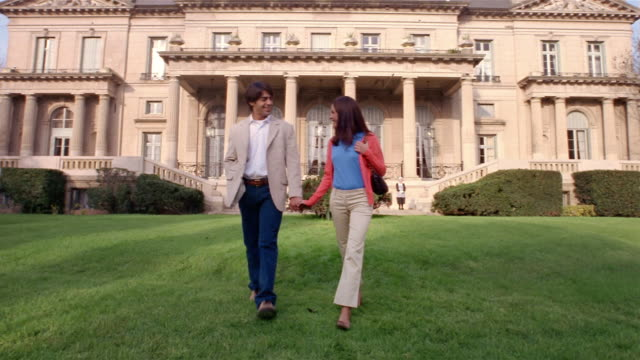 Wide shot young couple holding hands and walking on lawn in front of mansion / servants standing in background