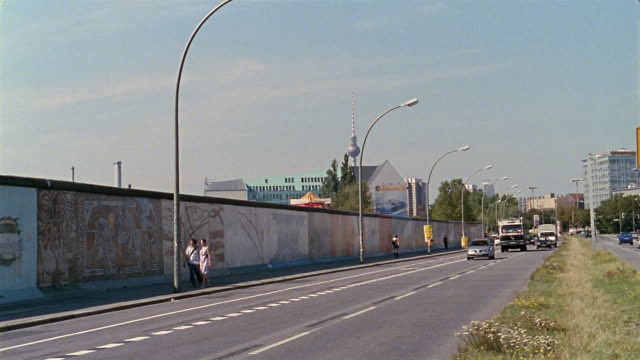 stockvideo's en b-roll-footage met wide shot young couple looking at murals while walking along the berlin wall next to traffic / germany - omwalling
