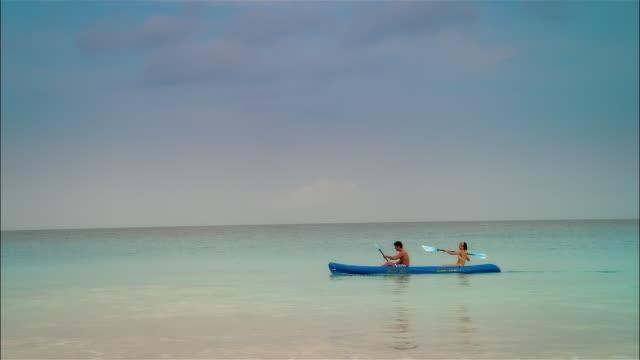 Wide shot Young couple paddling kayak in ocean/ Harbor Island, Bahamas