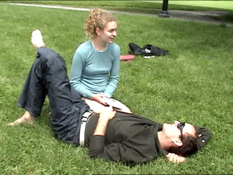 vidéos et rushes de wide shot young couple sitting on grass in park/ woman showing off her thumbs/ brooklyn - doigt humain