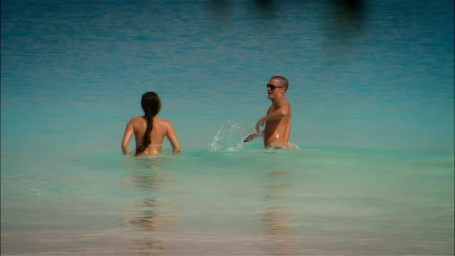 vídeos y material grabado en eventos de stock de wide shot young couple swimming in ocean during vacation/ harbor island, bahamas - bañador de hombre