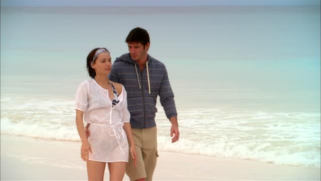 stockvideo's en b-roll-footage met wide shot young couple walking along beach/ harbor island, bahamas - noord atlantische oceaan
