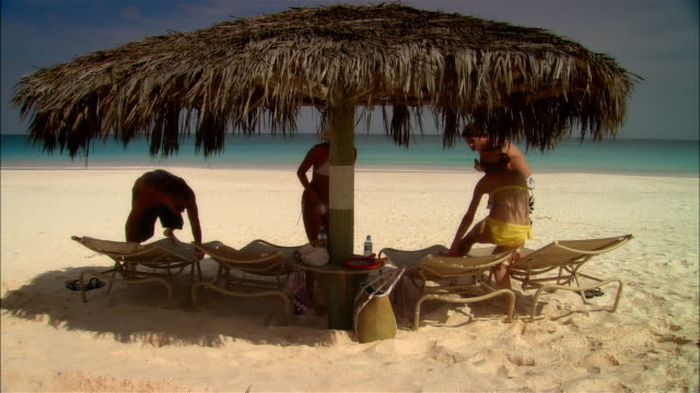 wide shot young couples relaxing on lounge chairs under palapa on beach during vacation/ harbor island, bahamas - mixed race person stock videos & royalty-free footage
