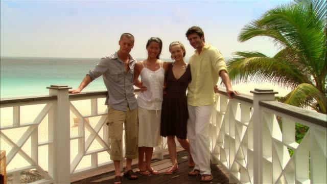 wide shot young couples standing on deck and smiling during vacation/ harbor island, bahamas - fyra människor bildbanksvideor och videomaterial från bakom kulisserna