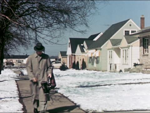 1953 wide shot young door to door sales man walking down sidewalk in snowy suburb carrying vacuum cleaner / audio - door to door salesperson stock videos & royalty-free footage