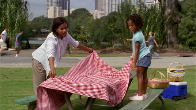 Wide shot young girl and mother spreading tablecloth on picnic table/ people walking + jogging in background/ Atlanta