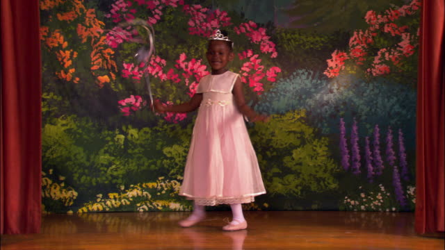 wide shot young girl wearing tutu and tiara dancing around and waving magic wand on stage / taking a bow - performer stock videos & royalty-free footage