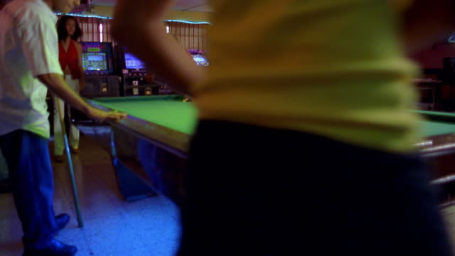 Wide shot young Hispanic men shooting pool around pool table / video games in background