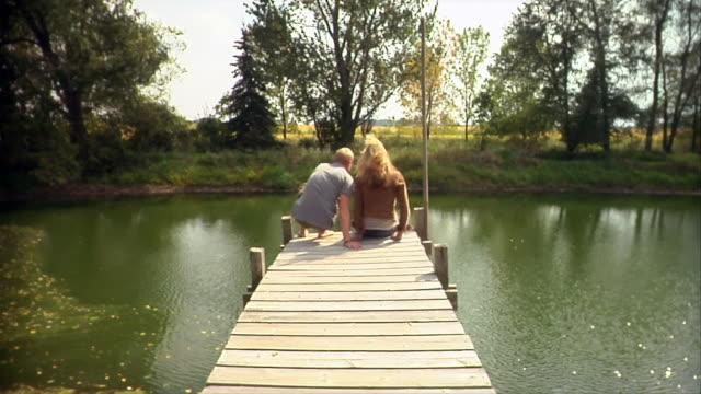 vídeos de stock e filmes b-roll de wide shot young man and young woman kissing near lake/ oshkosh, wisconsin, usa - sentar se