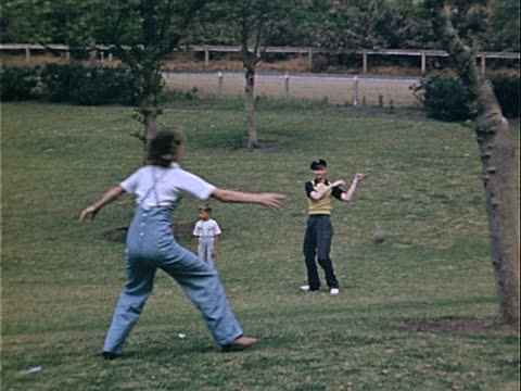 1939 Wide shot Young man batting and girl missing catch during family softball game in Griffith Park / Los Angeles, California, USA