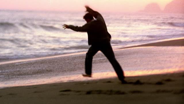 vídeos de stock e filmes b-roll de wide shot young man doing cartwheel on beach with ocean in background / california - pacífico norte