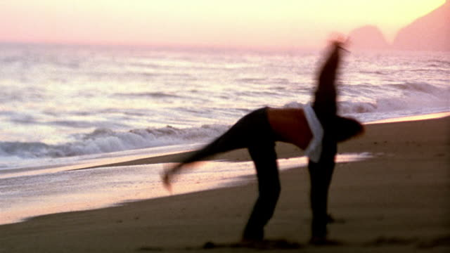 vídeos de stock e filmes b-roll de wide shot young man doing cartwheels on beach with ocean in background at dusk / california - pacífico norte
