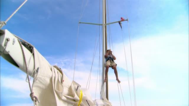 wide shot young man hoisting himself up sailboat mast on ropes/ harbor island, bahamas - 帆点の映像素材/bロール