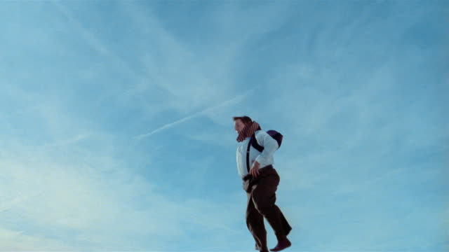 Wide shot young man in heavy businessman costume jumps on trampoline and does flips
