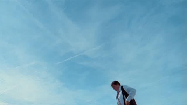 vídeos de stock e filmes b-roll de wide shot young man in heavy businessman costume jumps on trampoline and does flips - trampolim equipamento desportivo