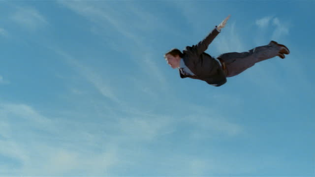 wide shot young man in suit jumping on trampoline and simulating flying - gesturing stock videos & royalty-free footage