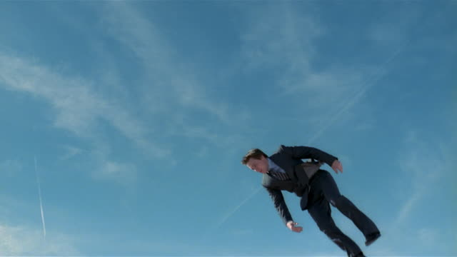 Wide shot young man in suit jumping on trampoline