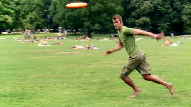 Wide shot young man running to catch frisbee in park / dropping frisbee / New York City